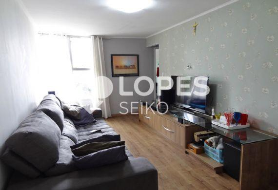 Cursino, Apartamento Padrão - Sala retangular com dois ambientes, piso laminado, papel de parede e teto com moldura de gesso.