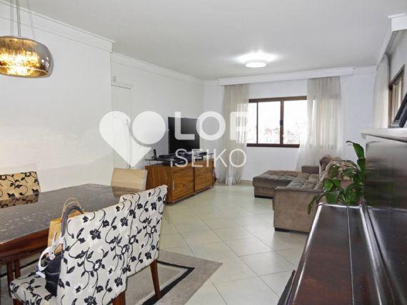 Saúde, Apartamento Padrão - Sala retangular com dois ambientes, piso de cerâmica, teto com moldura de gesso, cortineiro e acesso à varanda.