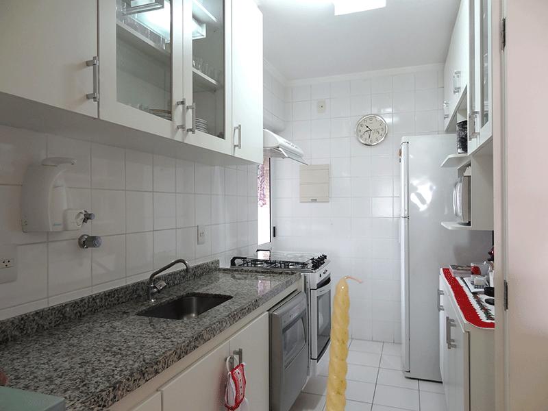 Ipiranga, Apartamento Padrão-Cozinha com piso de cerâmica, pia de granito com gabinete, armários planejados, teto com moldura de gesso e porta de alumínio na passagem para a área de serviço.