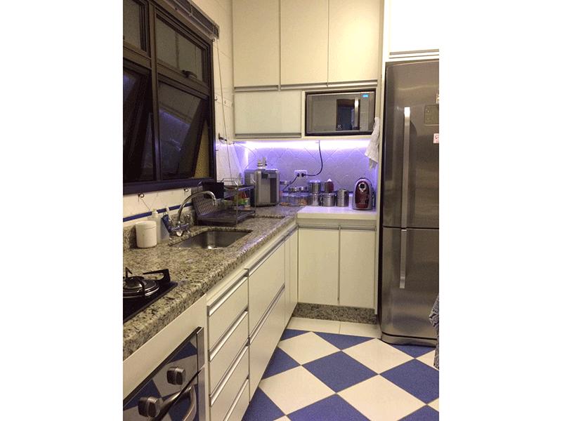 Sacomã, Apartamento Padrão-Cozinha com piso de cerâmica, pia de granito, gabinete, armários planejados e porta de madeira na passagem para a área de serviço.