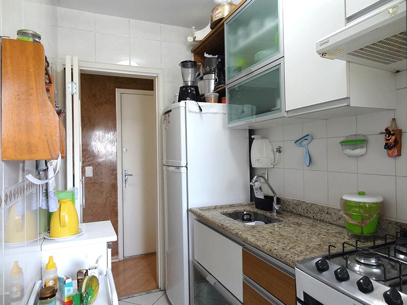 Ipiranga, Apartamento Padrão-Cozinha com piso de cerâmica, pia de granito, gabinete, armários planejados e porta de vidro na passagem para a área de serviço.