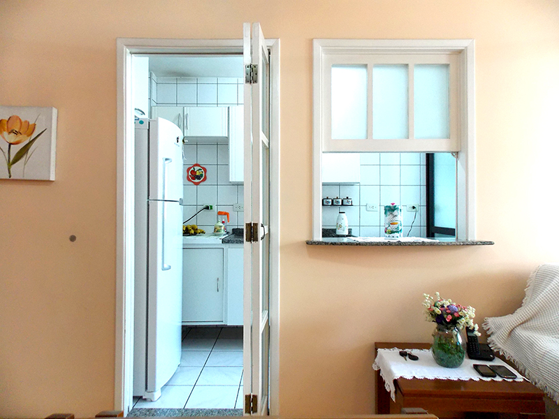 Jabaquara, Apartamento Padrão-Cozinha com piso de cerâmica e pia de granito, gabinete, armários planejados e porta de vidro na passagem para a área de serviço.