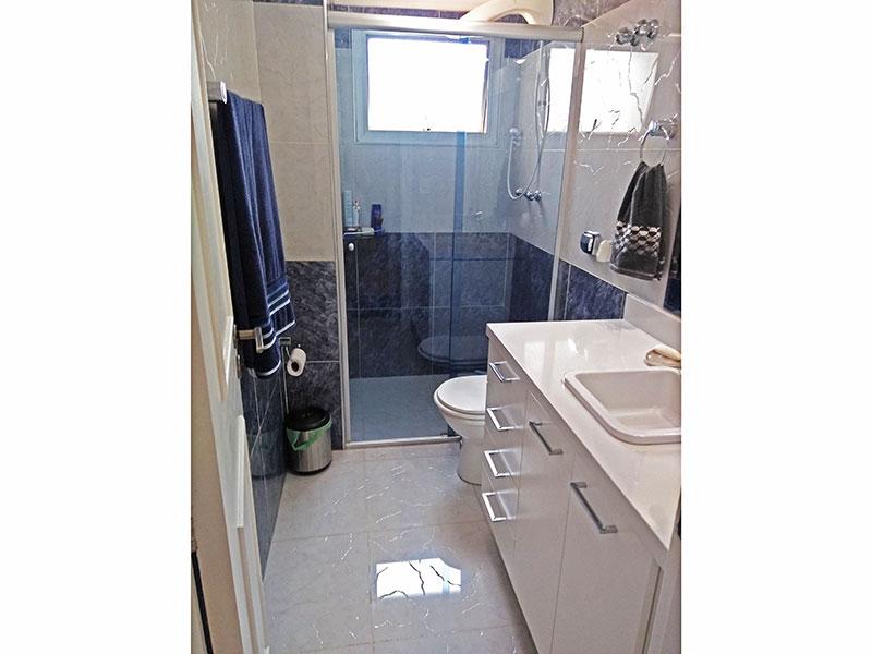 Jabaquara, Apartamento Padrão-Banheiro social com piso de porcelanato, teto com moldura de gesso, gabinete, pia de porcelana e box de vidro.