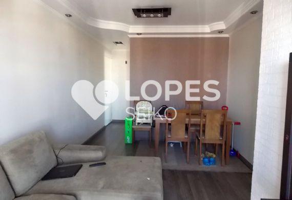 Jabaquara, Apartamento Padrão - Sala em L com sofá, piso laminado, teto com sanca de gesso e iluminação embutida, parede texturizada, e varanda com tela de proteção e guarda-corpo