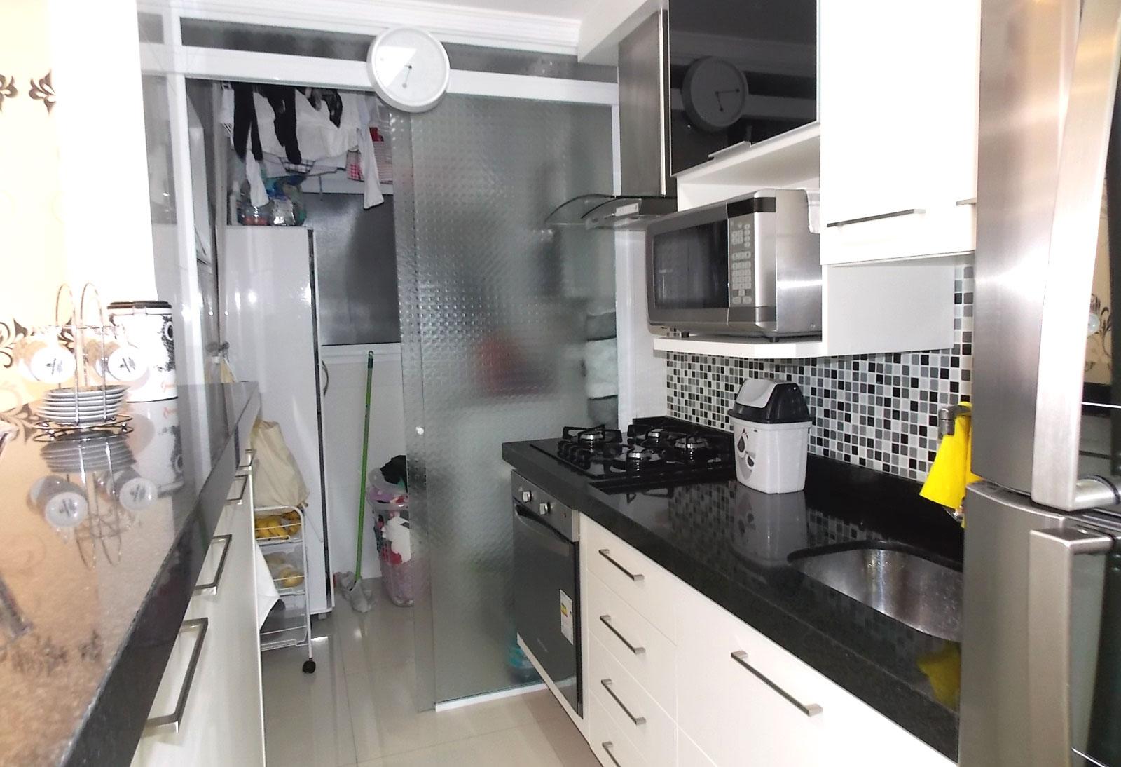Sacomã, Apartamento Padrão-Cozinha americana com piso de porcelanato, armários planejados, pia de granito, cooktop, coifa, forno e porta de vidro na passagem para área de serviço.