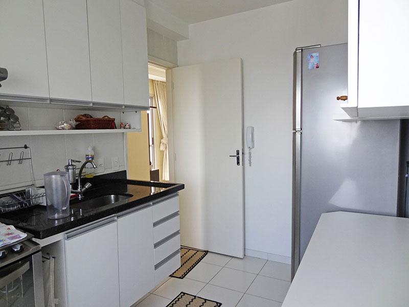 Sacomã, Apartamento Padrão-Cozinha com piso de cerâmica, armários planejados, pia de granito e porta de vidro na passagem para a área de serviço.