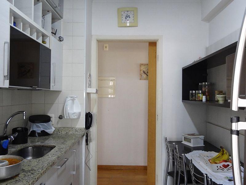 Ipiranga, Apartamento Padrão-Cozinha com piso de cerâmica, armários planejados, pia de granito e porta de vidro na passagem para a área de serviço.