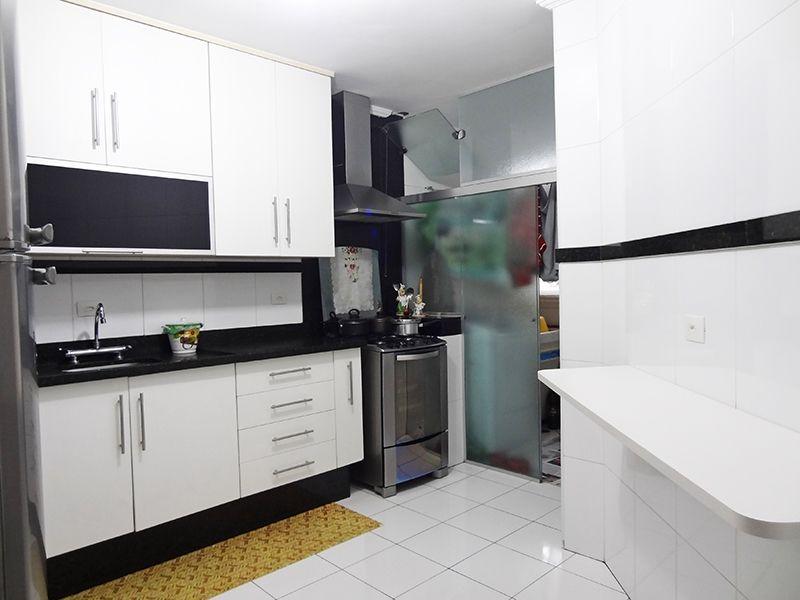 Jabaquara, Apartamento Padrão-Cozinha com piso de cerâmica, armários planejados, pia de granito e porta de vidro na passagem para a área de serviço.