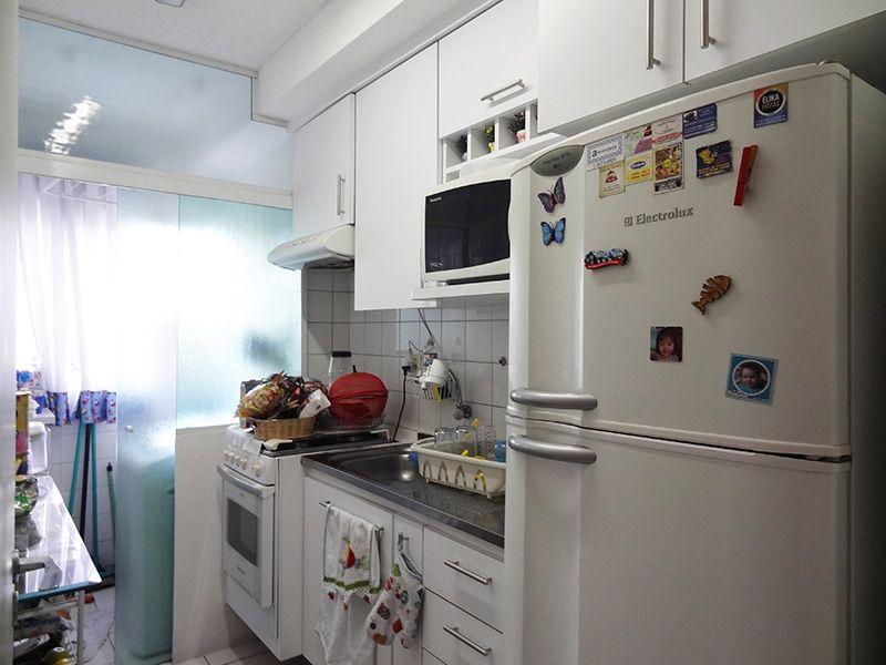 Sacomã, Apartamento Padrão-Cozinha americana com piso de cerâmica, pia de granito com gabinete, armários e porta de vidro na passagem para a área de serviço.