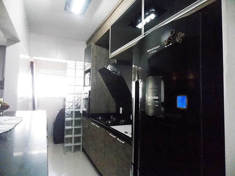 Ipiranga, Apartamento Padrão-Cozinha americana com piso de porcelanato, pia quartzo com gabinete, armários e parede de vidro na passagem para a área de serviço.