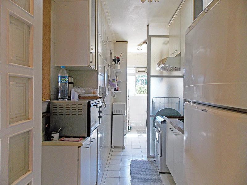Jabaquara, Apartamento Padrão-Cozinha com piso de cerâmica, pia de granito, armários planejados, teto com moldura de gesso e porta de vidro na passagem para a área de serviço.