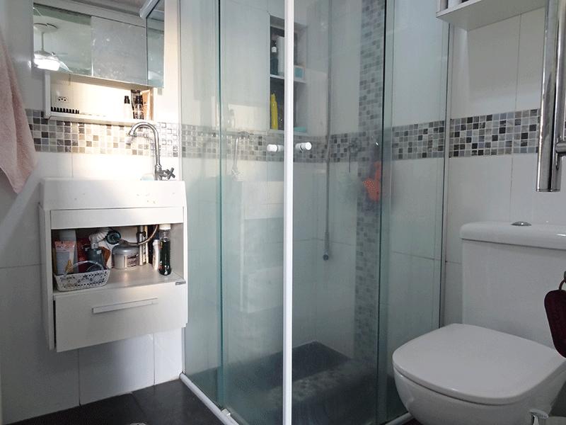 Jabaquara, Apartamento Padrão-Banheiro da suíte com piso de porcelanato, teto com moldura de gesso, pia de porcelana com gabinete e box de vidro.