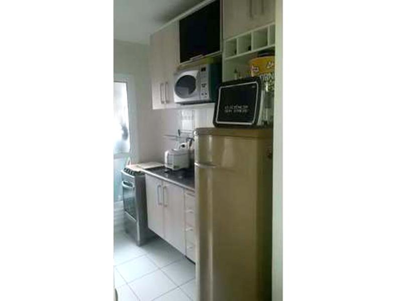 Sacomã, Apartamento Padrão-Cozinha americana com piso de cerâmica, pia de granito com gabinete e armários e porta de vidro na passagem para a área de serviço.