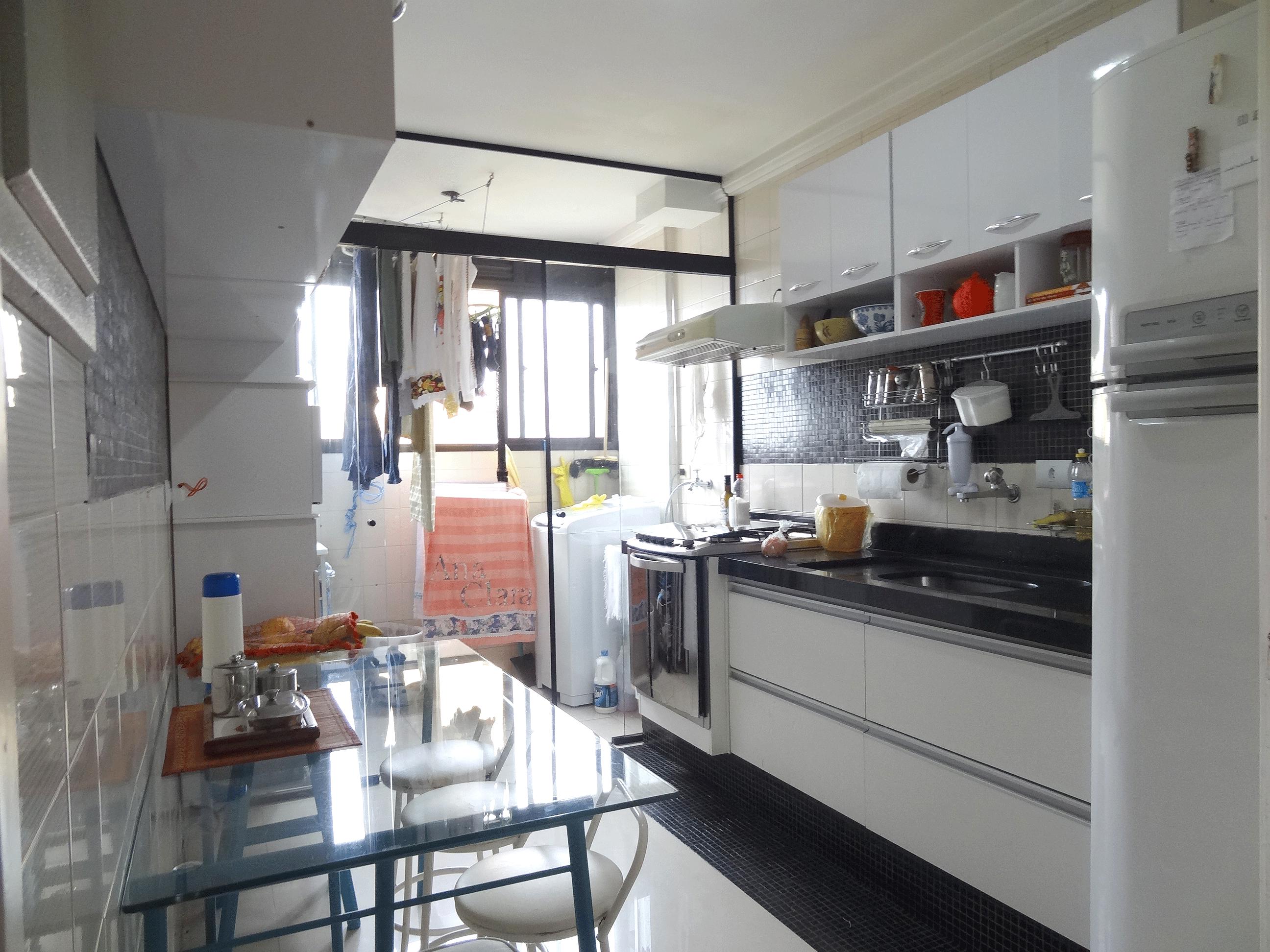 Jabaquara, Apartamento Padrão-Cozinha com piso de porcelanato, pia de mármore, gabinete, armários planejados e porta de vidro na passagem para a área de serviço.