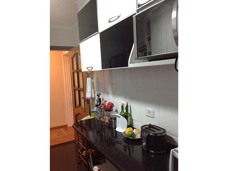 Ipiranga, Apartamento Padrão-Cozinha piso porcelanato, pia de granito, coifa, armários planejados e porta de vidro na passagem para a área de serviço.