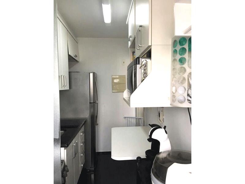 Sacomã, Apartamento Padrão-Cozinha com piso de porcelanato pia de granito, armários planejados e porta de vidro na passagem para a área de serviço.