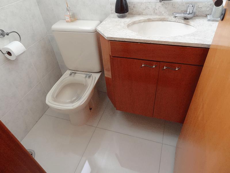 , -Lavabo com piso de porcelanato, teto de espelho, pia de mármore e gabinete.