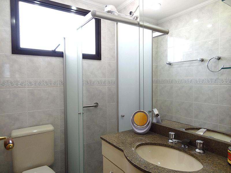 , -Banheiro social com piso de porcelanato, teto com moldura de gesso, pia de granito, gabinete e box de vidro.