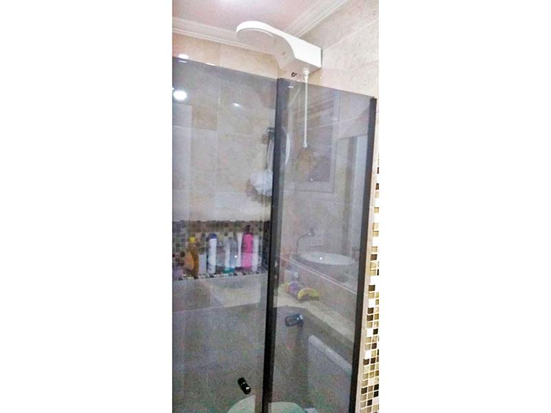 Jabaquara, Apartamento Padrão-Banheiro social com piso de porcelanato, teto com moldura de gesso, gabinete, pia sobreposta e box de vidro.